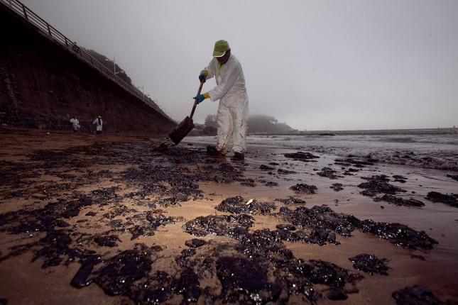 Un operario recoge fuel vertido por la térmica de Aboño en Candás. 26 de junio de 2012. © Miki López/La Nueva España