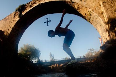 Un niño salta al agua bajo el puente romano de Cangas de Onís. 12 de septiembre de 2013. © Miki López