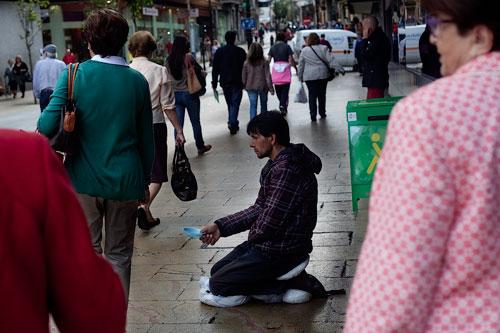 Un hombre pide limosna en la calle de La Cámara. Avilés, 18 de octubre de 2013. © Miki López