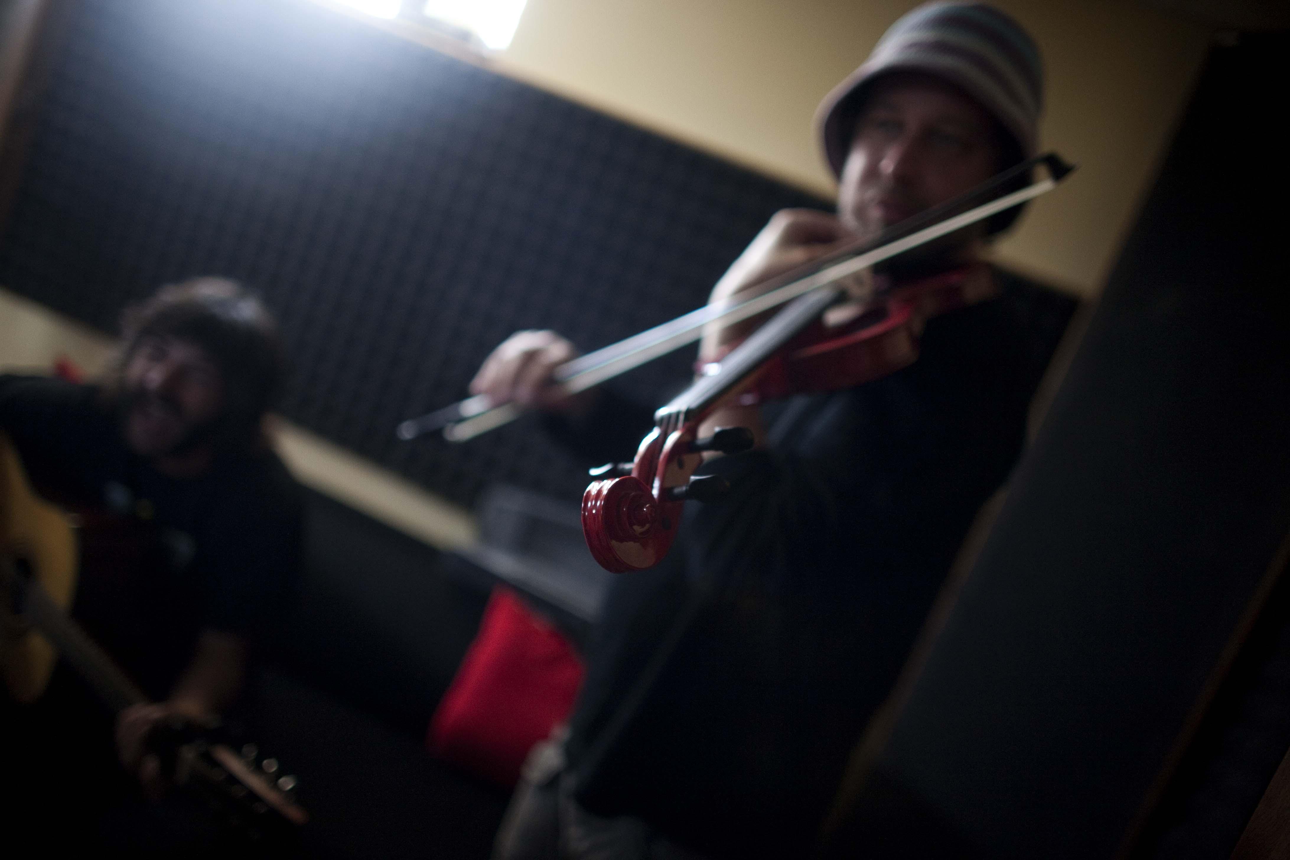 Lisardo afina el violín durante un ensayo con N'arba. Perdones (Gozón). 2013.  © Miki López