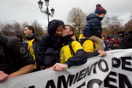 Un trabajador de Alcoa besa a su hija en la Plaza de España tras la marcha a pie que llevaron a cabo desde la factoría de Avilés. © Miki López