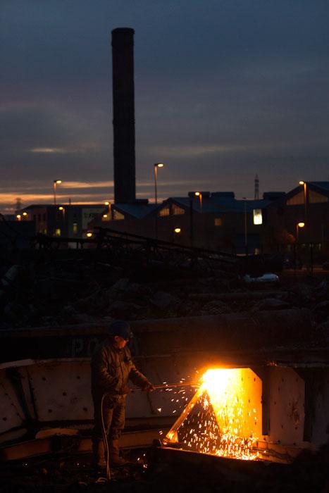 Un trabajador corta a soplete los restos de uno de los gasómetros de Llaranes. Avilés, 3 de enero de 2007. © Miki López